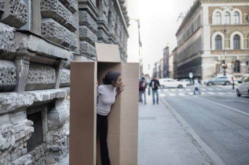 photo of woman peeking out of cardboard box near city street